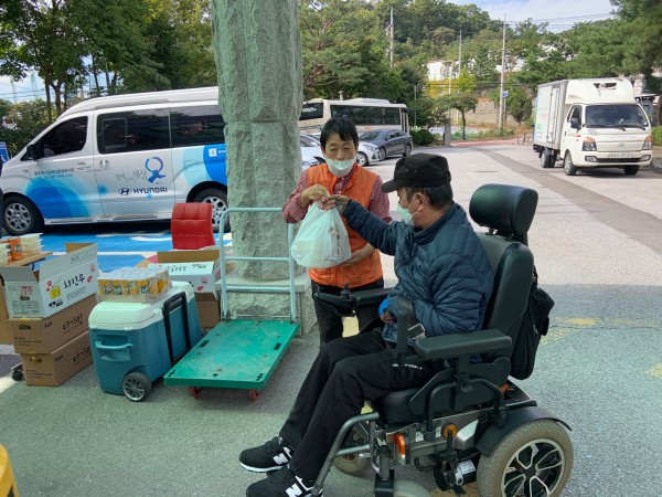 휠체어를 타고있는 장애인에게 치킨을 챙겨주는 직원